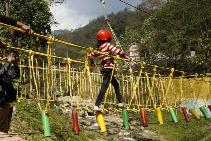 Parents encouraging their daughter during rope challenge activity in Gangtok